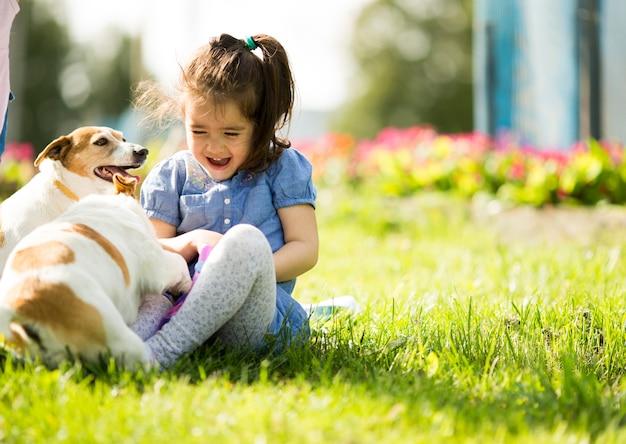 Kleines mädchen, das mit hunden spielt