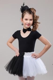 Kleines mädchen, das mit ihrem bein oben im tanzenden kostüm aufwirft.
