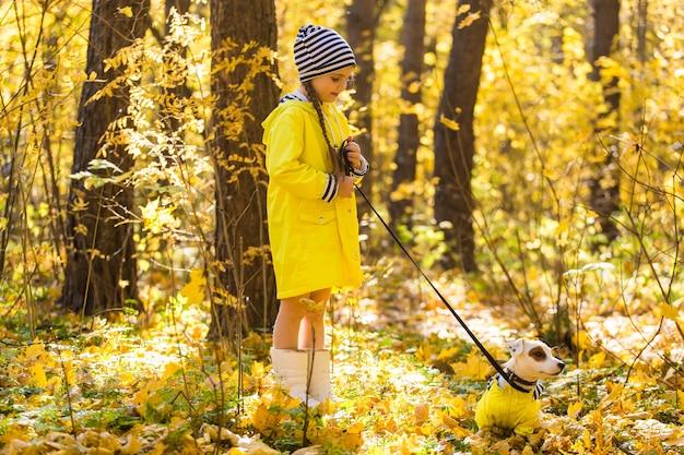 Kleines mädchen, das mit ihrem hund im herbstwald spielt