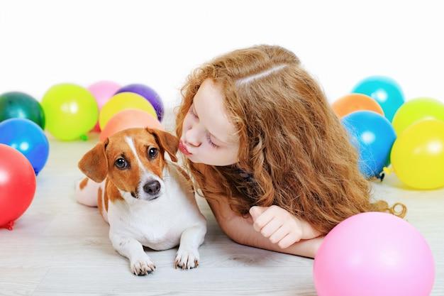 Kleines mädchen, das mit ihrem jack russell-terrier in der geburtstagsfeier küsst.