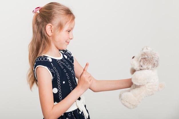 Kleines mädchen, das mit ihrem teddybären spricht