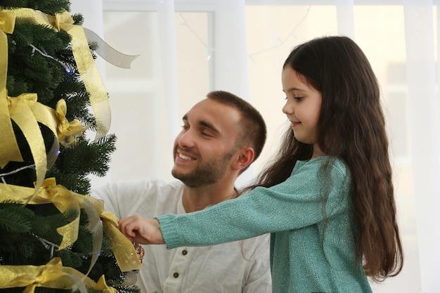Kleines mädchen, das mit ihrem vater den weihnachtsbaum schmückt