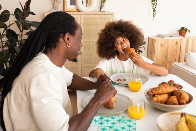 Kleines mädchen, das mit ihrem vater frühstückt
