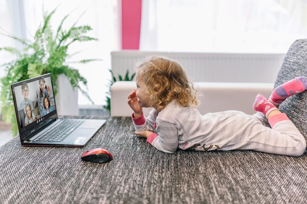Kleines mädchen, das mit ihren freunden auf einem laptop im videoanruf spricht