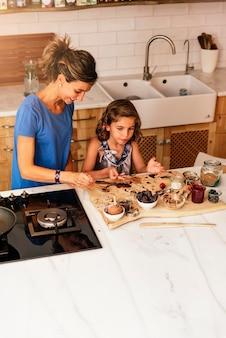 Kleines mädchen, das mit ihrer mutter in der küche kocht. konzept des säuglingskochs.