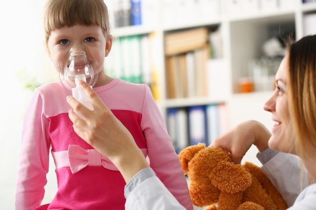 Kleines mädchen, das mit inhalator in der arztpraxis atmet