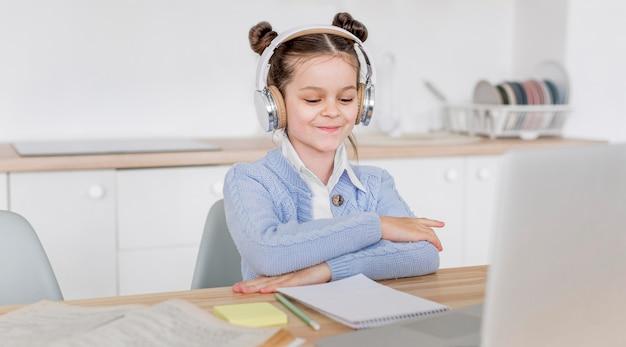 Kleines mädchen, das mit kopfhörern studiert