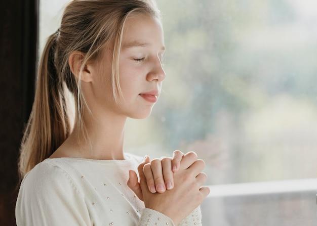 Kleines mädchen, das mit kopienraum betet