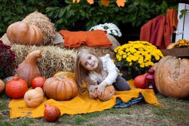 Kleines mädchen, das mit kürbis bei halloween spielt