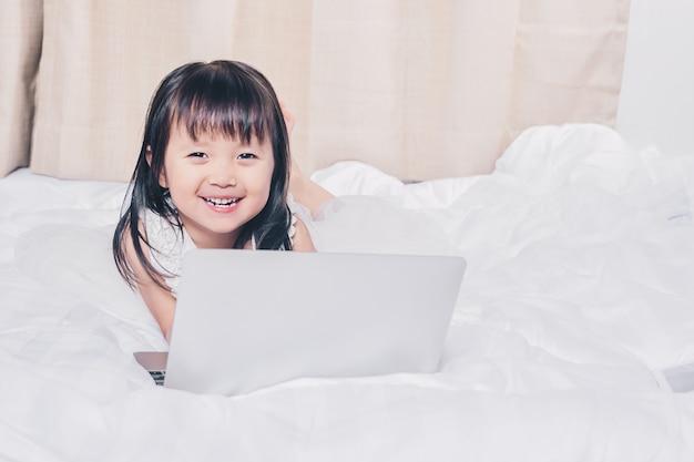 Kleines mädchen, das mit laptop auf dem glücklichen lächeln des betts mit dem internet-überwachen liegt