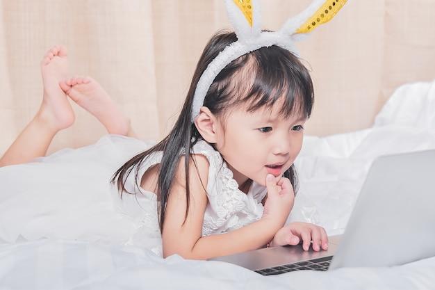 Kleines mädchen, das mit laptop auf dem glücklichen lächelnden denken des betts mit technologiekonzept liegt