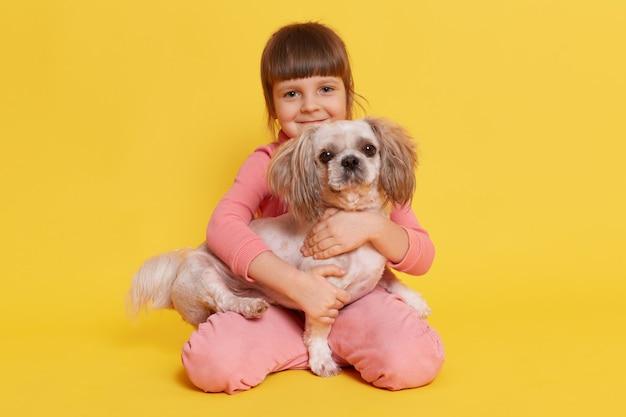 Kleines mädchen, das mit pekinesischem hund auf gelb aufwirft
