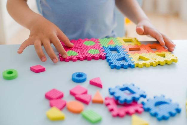 Kleines mädchen, das mit puzzlespiel, früherziehung spielt