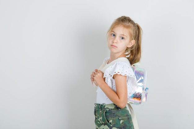 Kleines mädchen, das mit rucksack im weißen t-shirt aufwirft
