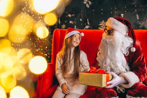 Kleines mädchen, das mit sankt und geschenken auf weihnachten sitzt
