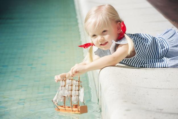 Kleines mädchen, das mit segelboot spielt