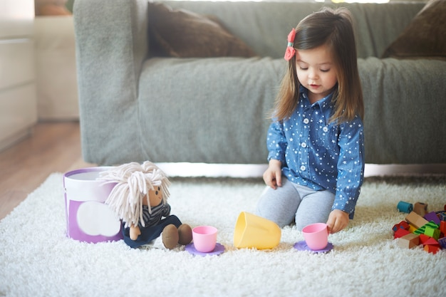 Kleines mädchen, das mit spielzeug am wohnzimmer spielt