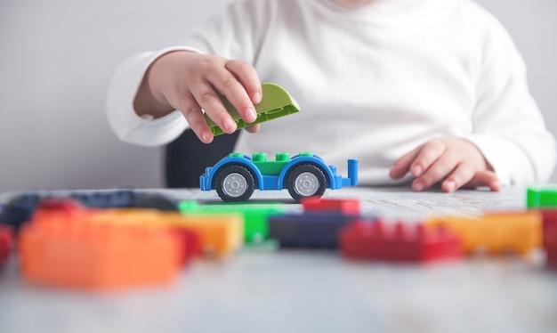 Kleines mädchen, das mit spielzeugauto spielt.