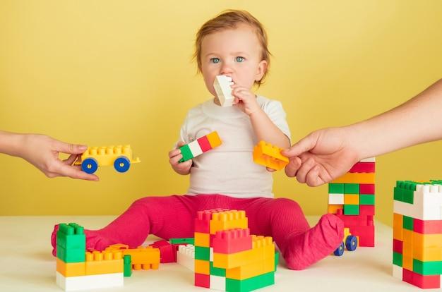 Kleines mädchen, das mit spielzeugblöcken spielt