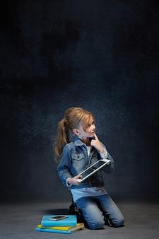 Kleines mädchen, das mit tablette im grauen studio sitzt