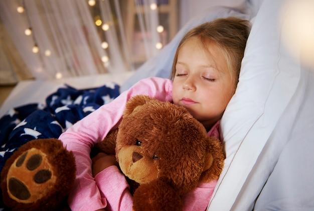 Kleines mädchen, das mit teddybär schläft