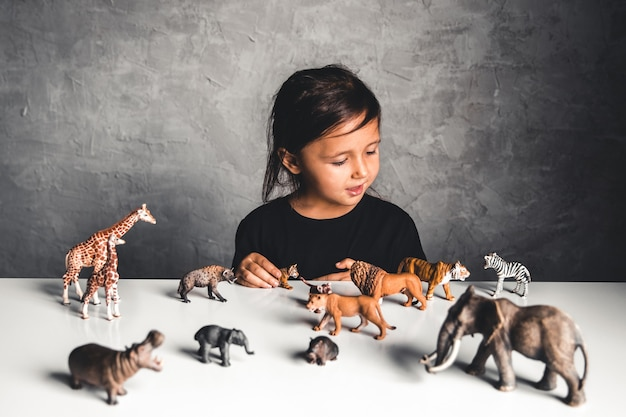 Kleines mädchen, das mit tierspielzeug im spielzimmer spielt
