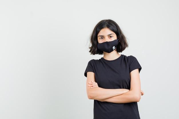 Kleines mädchen, das mit verschränkten armen im schwarzen t-shirt, in der maske steht und vernünftig aussieht. vorderansicht.