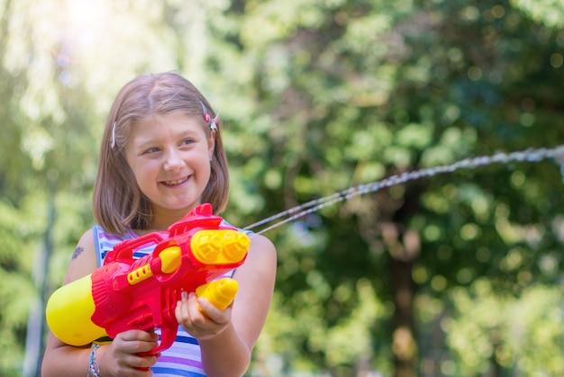 Kleines mädchen, das mit wasserpistole im park an einem sonnigen tag spielt