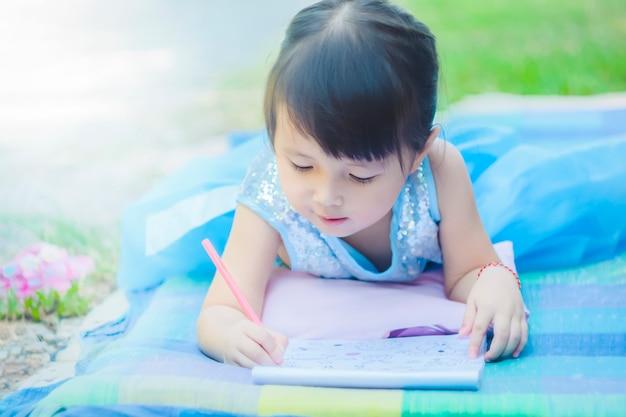 Kleines mädchen, das mit zeichnungsbuch auf matte im park mit glücklichem gesicht liegt, wenn relaxant im mornin