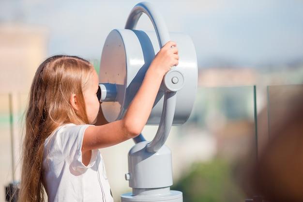 Kleines mädchen, das münzbetriebenes fernglas auf terrasse mit schöner ansicht betrachtet