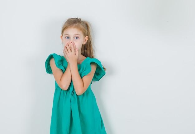 Kleines mädchen, das mund mit händen im grünen kleid bedeckt und überrascht schaut. vorderansicht.