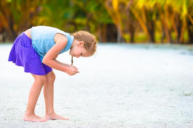 Kleines mädchen, das muscheln auf weißem sandstrand sammelt