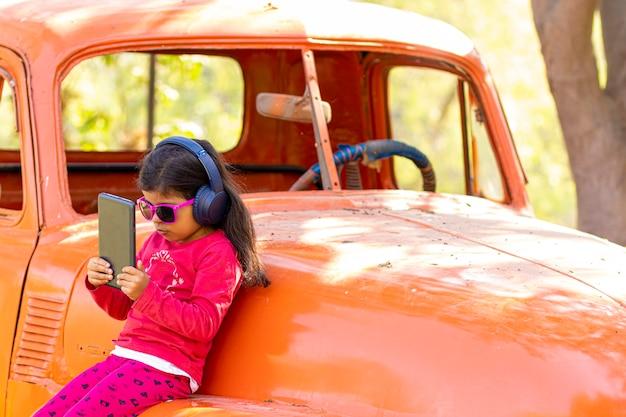Kleines mädchen, das musik auf der tablette mit ihren kopfhörern in einem lkw-auto hört