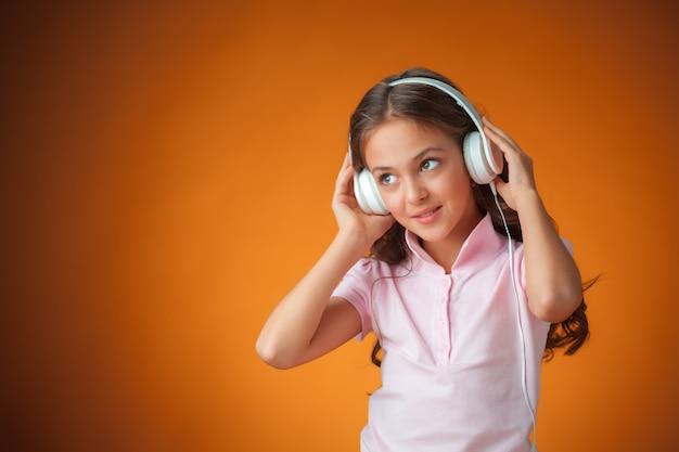 Kleines mädchen, das musik auf ihren kopfhörern hört