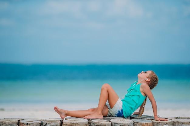 Kleines mädchen, das musik auf kopfhörern am karibischen strand hört