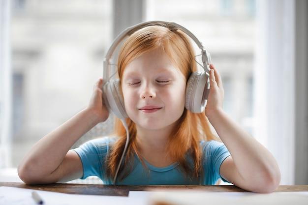 Kleines mädchen, das musik auf kopfhörern hört