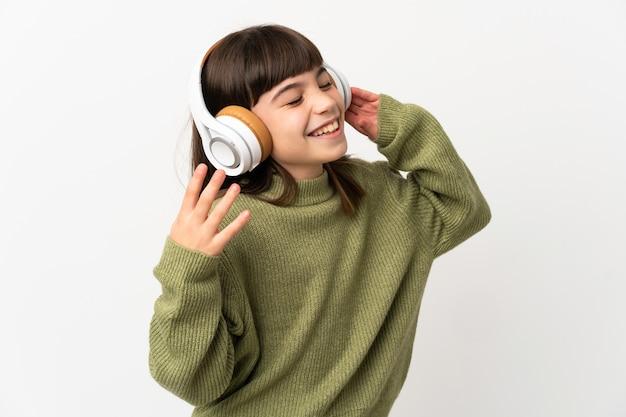 Kleines mädchen, das musik mit einem handy hört, das auf weißem hintergrund lokalisiert ist, der musik hört und singt