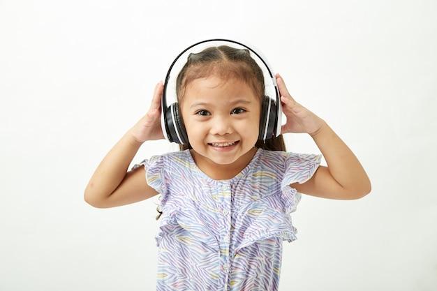 Kleines mädchen, das musik über kopfhörer hört