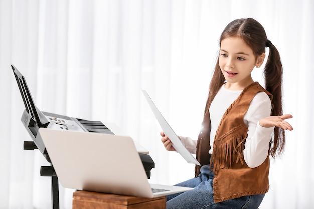 Kleines mädchen, das musikunterricht online zu hause nimmt