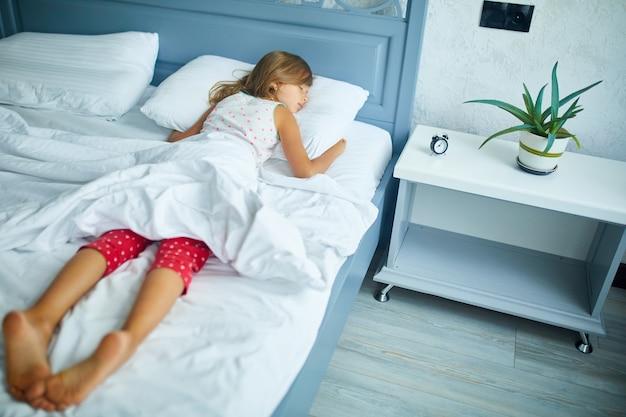 Kleines mädchen, das nachmittags zu hause auf einem großen und gemütlichen bett mit weißer bettwäsche schläft