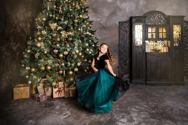 Kleines mädchen, das nahe dem weihnachtsbaum lächelt und tanzt. konzept des glücks und der neujahrsferien.