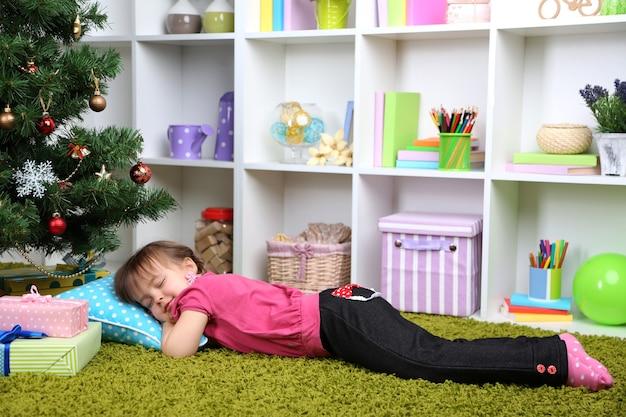 Kleines mädchen, das nahe weihnachtsbaum im zimmer schläft