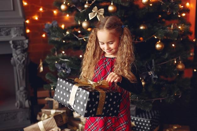 Kleines mädchen, das nahe weihnachtsbaum mit geschenk steht