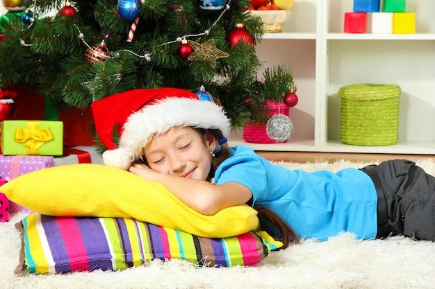 Kleines mädchen, das nahe weihnachtsbaum schläft