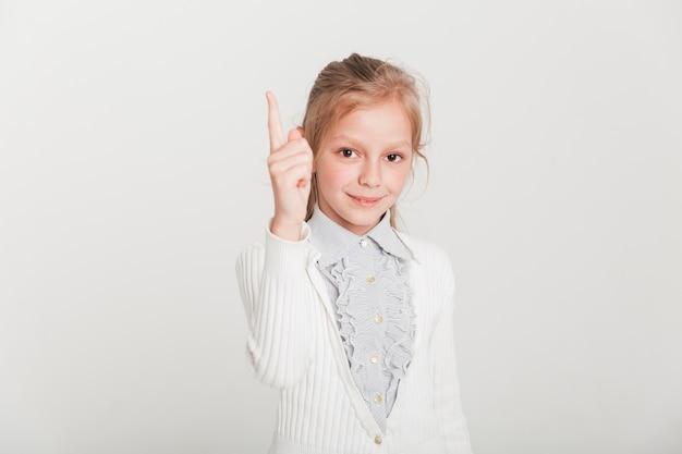 Kleines mädchen, das oben mit dem finger zeigt