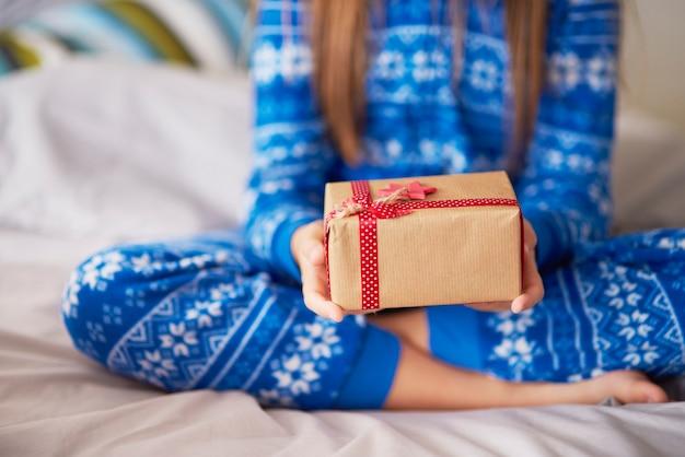 Kleines mädchen, das ökologisches weihnachtsgeschenk hält