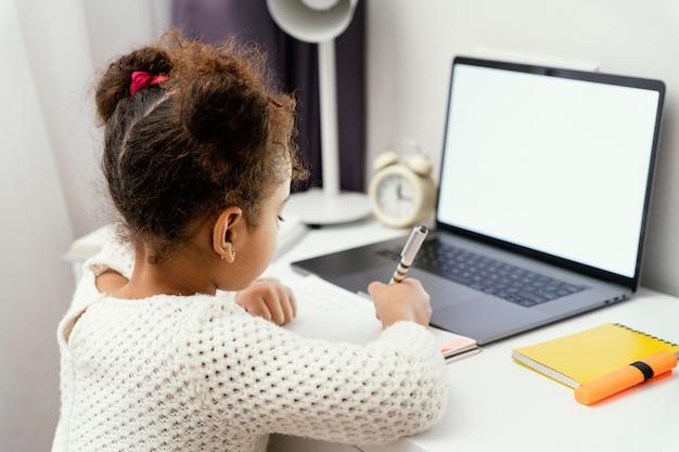Kleines mädchen, das online-schule zu hause mit laptop besucht
