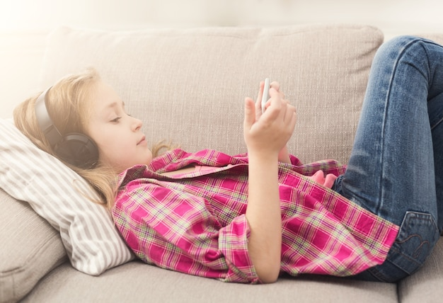 Kleines mädchen, das online-spiele auf dem smartphone spielt und musik über kopfhörer hört und zu hause auf dem sofa liegt. moderne technologien sucht und social-networking-konzept, kopienraum