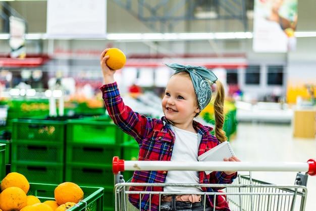 Kleines mädchen, das orangen am supermarkt heraussucht