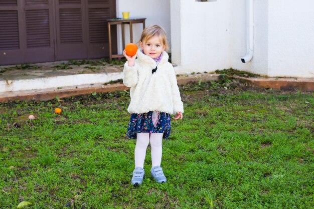 Kleines mädchen, das orangen im garten hält